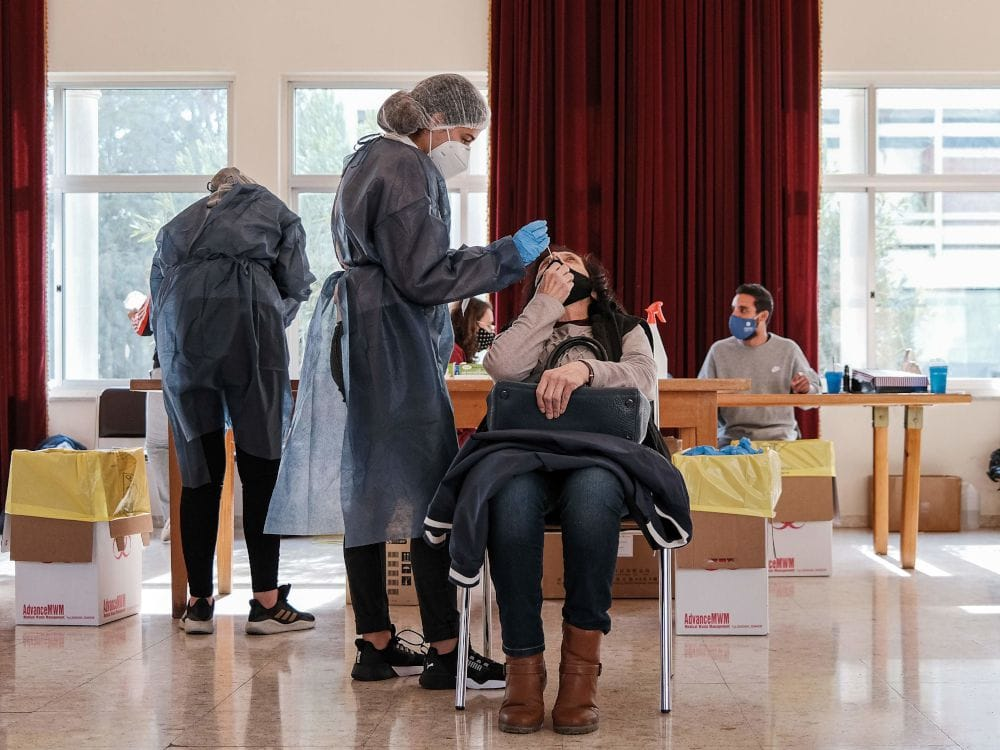 A medical worker performs a COVID-19 swab test upon a woman at a rapid-testing station at the Panagia Evangelistria Greek Orthodox Church in Cyprus' capital Nicosia on Jan. 29. PHOTO BY AMIR MAKAR/AFP